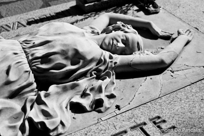Tomba di Isa Bluette, Campo Primitivo Ovest. Una ballerina distesa a terra, i piedi nudi, le braccia sopra la testa, i capelli sciolti, gli occhi chiusi e le labbra increspate da un lieve sorriso… è Isa Bluette, al secolo Teresa Ferrero, ritratta da Giacomo Giorgis. La sua storia è molto romantica: è stata la più grande soubrette della rivista italiana nella prima metà del '900. Scopritrice di Macario e Totò, morì di tisi a 41 anni nel 1939. Il compagno della vita, l'attore Nuto Navarrini, volle sposarla sul letto di morte ed è sepolto insieme a lei.
