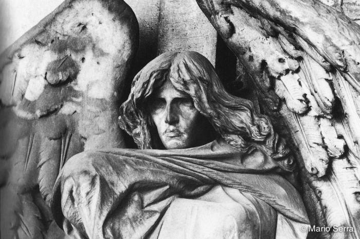 Tomba Braida, II ampliazione. Il Cimitero di Staglieno custodisce il fascino androgino dell'Angelo della Morte di Giulio Monteverde, forse l'opera di arte funeraria più famosa del mondo. Il Cimitero di Torino non è però da meno! Sotto i suoi porticati si trova lo stupendo e inquietante Angelo della Morte di Leonardo Bistolfi. A guardia di una culla vuota, è avvolto da un ampio panneggio, i capelli lunghi scompigliati… distante e imperturbabile, è espressione pura del mistero del Nulla. Purtroppo ora è in pessime condizioni.