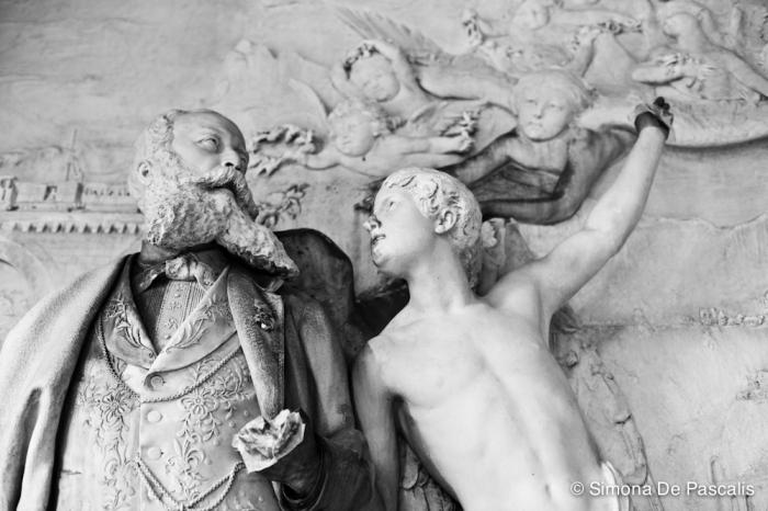 """Tomba Pongiglione, IV ampliazione. Un monumento ricchissimo di particolari legati alla simbologia funeraria. Ogni volta che lo si osserva sembra sempre che spunti un nuovo dettaglio: rane, falene, civette, topi… soprannominata """"tomba d'j rat"""", è stata progettata dal committente, l'ingegnere e filantropo Giuseppe Pongiglione, che si è fatto raffigurare dallo scultore Lorenzo Vergnano, mentre esce dalla bara e si accinge a salire in cielo accompagnato da un angelo e dallo scrigno dei Ricordi stretto in mano."""