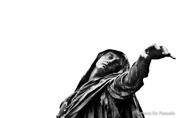 Tomba Remondini (ora Tomba Italiano), III ampliazione Nord. Guardandola di sfuggita, si potrebbe scambiare per una persona in carne e ossa che si aggira tra le tombe. Osservandola con più attenzione, si scopre che quella figura di donna è in bronzo ed è stata realizzata da Edoardo Rubino. Ferma con il braccio disteso nel gesto dell'estremo saluto, sola e isolata in mezzo agli altri monumenti, ha il potere di trasportare chi le si trova di fronte fuori dal tempo e dallo spazio e di comunicare con tutta la sua forza espressiva la malinconia e l'imperscrutabilità della Morte.