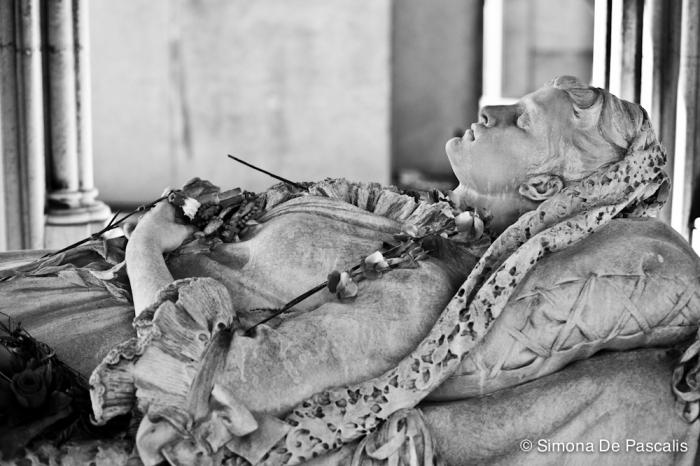 """Tomba Denina Sineo, I ampliazione. Doveva essere davvero bella Teresa Denina, morta a 27 anni nel 1883. Il suo monumento funebre è conosciuto per essere quello della """"sposa bambina"""". Scolpita da Odoardo Tabacchi, sembra solo addormentata, distesa sotto un imponente baldacchino e sorvegliata da piccole statue di angeli decapitati dai vandali. La sua giovinezza è stata fissata per sempre nel candore del marmo, che contrasta con i colori vivaci dei fiori, appoggiati sul suo petto da pietose mani sconosciute."""