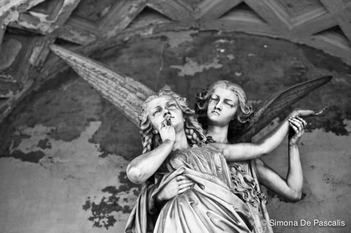 Tomba Toesca di Castellazzo, II ampliazione. Da un sarcofago circondato da quattro puttini, sorretta da un angelo protettivo, si alza in volo la giovane Giuseppina Garbiglietti. Due trecce tra i folti capelli sciolti, avvolta da un grande mantello, avvicina una mano alla bocca per mandare un ultimo bacio a coloro che restano. Ai suoi fianchi, i busti del padre Antonio e del marito Gioacchino Toesca di Castellazzo, che segue con lo sguardo la moglie volare via, sicuro nella sua speranza di rincontrarla nell'Altrove.