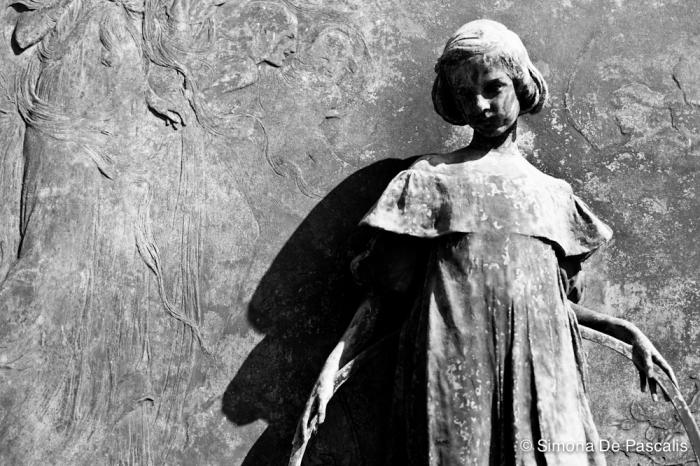 Tomba Vigo, Campo Primitivo Est. «Ella giocava per le pinte aiole… l'ombra l'avvolse…»  recita l'epigrafe tratta da una poesia di Giosuè Carducci. Il monumento, opera di Pietro Canonica, è tutto dedicato alla piccola Laura Vigo, morta nel 1907 a 9 anni. La bimba ha messo dietro la schiena il suo cerchio, ha finito di giocare. Ascolta la voce degli angeli vicini a lei e, grazie alla sensibilità che solo i bambini riescono ad avere, sa già di non essere più parte di questo mondo.