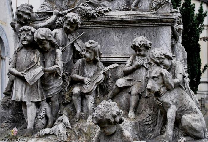 Monumento Ulisse Merini, Reparto IV Quella di Ulisse Merini è forse la tomba che preferisco, anche per la mia passione per il mondo animale. Si tratta della sepoltura di un benefattore che lasciò i propri averi in donazione a centri di aiuto infantile di Milano e provincia. Un coro e un concerto di bimbi ne onorano la memoria. Dalla tomba emergono i temi dell'amore per l'infanzia e l'inclinazione verso la natura e gli animali, come si può ad esempio vedere sulla destra, osservando la dolcezza del bimbo che abbraccia un cane.