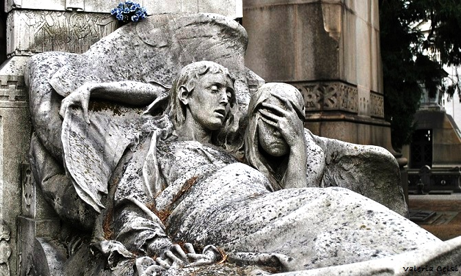 """Monumento Zaira Brivio, Reparto I Avete presente le foto post mortem del celebre film """"The Others"""" con Nicole Kidman? Ebbene, questa sepoltura mi ricorda proprio quel film: la giovane Zaira adagiata sul letto di morte è ritratta col volto e il corpo distrutti dall'agonia, con un inquietante rimando alla fotografia post mortem collocata ai piedi del letto. Un angelo partecipa al dolore per questa morte prematura. Da notare il fumo della candela modellato in granito che si eleva in cielo assieme all'anima della giovane."""