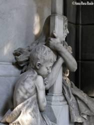 Tomba Croce, scultore Luigi Beltrami, 1899, porticato inferiore nord-est I Croce erano una stimata famiglia di negozianti. Il monumento venne prima collocato nel 1894, con la sola statua femminile avvinta alla croce, bellissima ed espressiva. In seguito, il figlio superstite, in memoria del genitore, morto nel 1897, fece aggiungere la statua del fanciullo, che rappresenta la preghiera dell'innocenza.