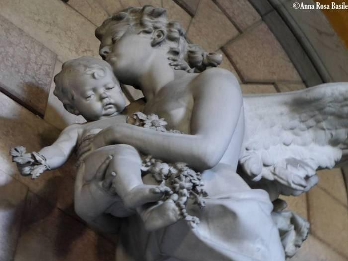 Tomba Montebruno, scultore Demetrio Paernio, 1886, porticato inferiore Una delle mie opere preferite, un angelo custode si libra in volo portando in braccio un bimbo ornato da un festone fiorito, in un atteggiamento molto materno.
