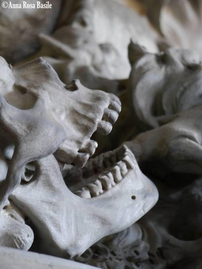 Tomba di Salvatore Queirolo, scultore Luigi Navone, 1901, porticato inferiore Il motto sulla tomba dice: «Fulminata è la morte, Eterno impero il regno della Vita». La donna rappresenta la vita eterna che sconfigge la morte che si dibatte impotente. Particolare del teschio.