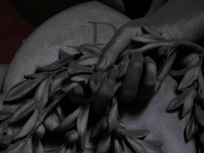 Tomba David Raggio, scultore Demetrio Parnio, S.D.-porticato inferiore lato est Commissionata allo scultore dalla vedova del famoso commerciante, rappresenta uno dei tanti angeli dello scultore: bello, slanciato e malinconico, nella mano destra regge un ramo reciso e sembra pregare per l'anima del defunto.